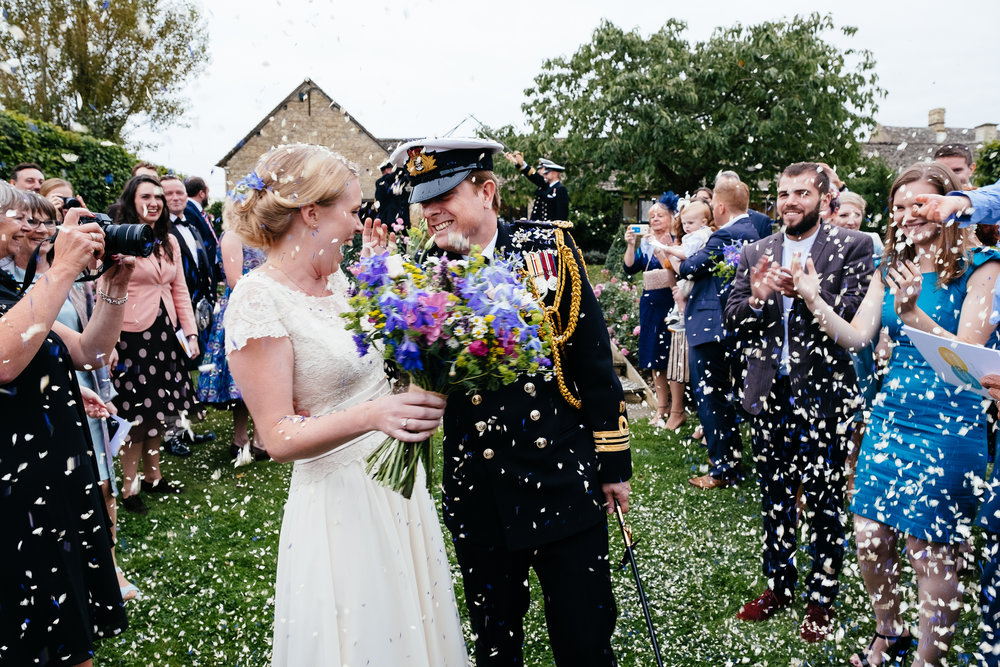 A bride and groom get covered in confetti at Merriscourt Wedding Venue, Oxfordshire