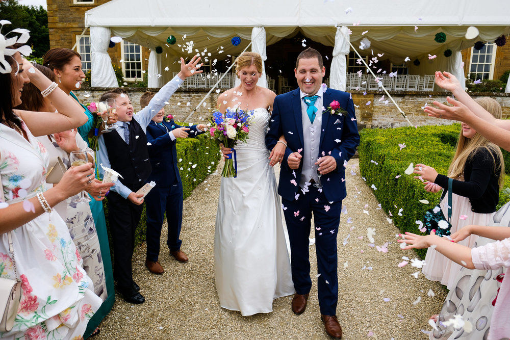 A bride and groom covered in confetti at a wedding at Poundon House, Near Bicester Oxfordshire