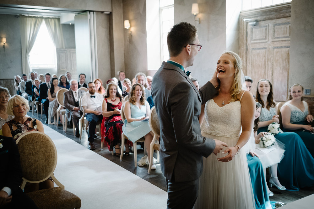 A bride and groom smiling in their wedding ceremony at Fawsley Hall, Northamptonshire