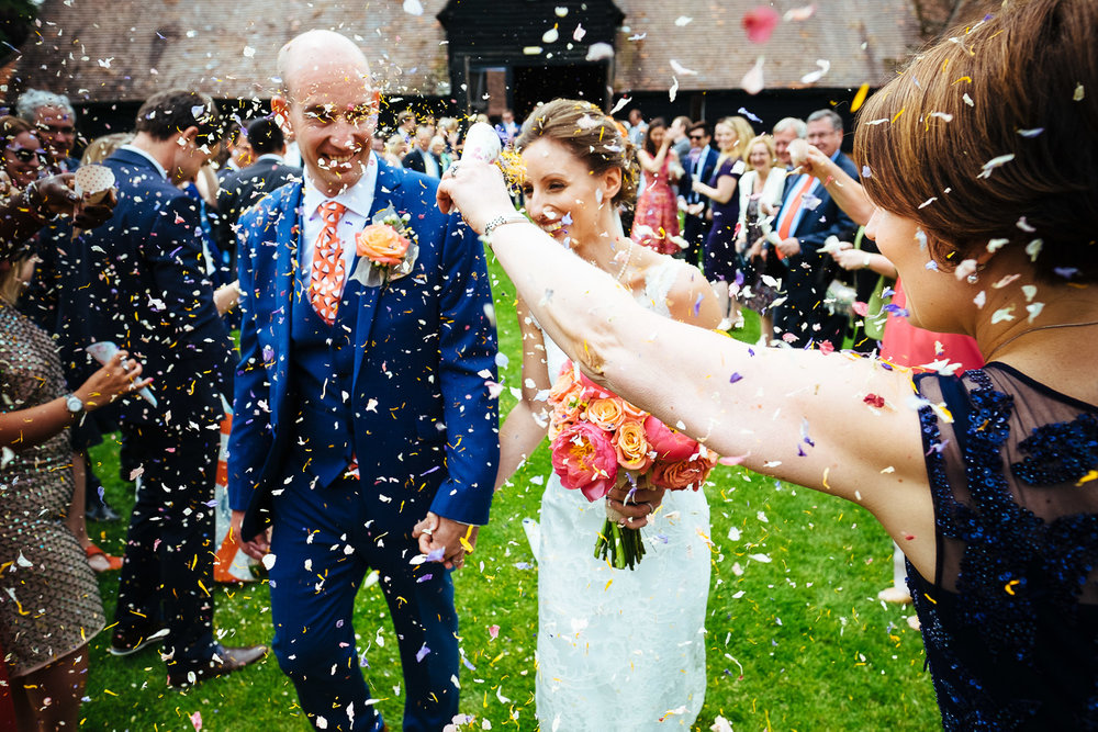 Lains Barn wedding photograph showing a bride and groom being showered in confetti