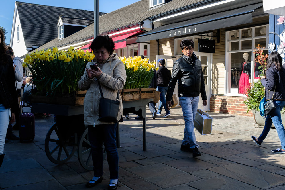 A woman checks her phone at Bicester Village Outlet Centre