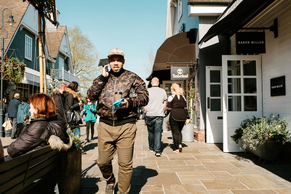 A man using his mobile phone at Bicester Village Outlet Village