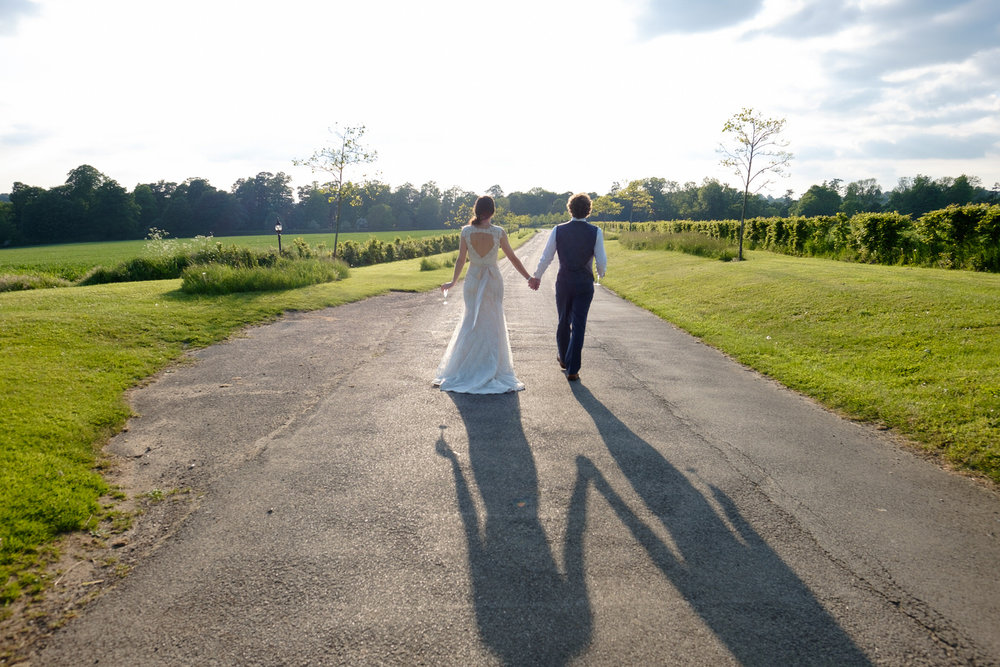 A bride and groom walking at Great Barn Wedding Venue, Aynho. Photo by Sam and Steve Photography