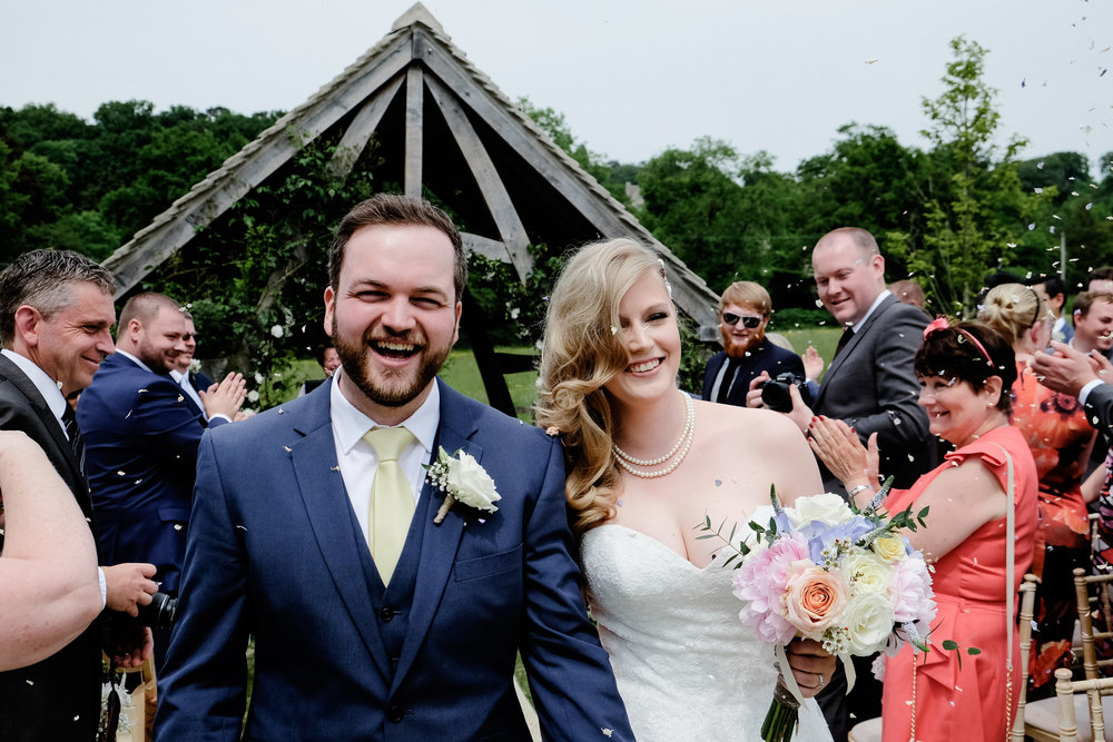 Bride and Groom covered in confetti during their wedding at Hyde Barn, Stow on the Wold