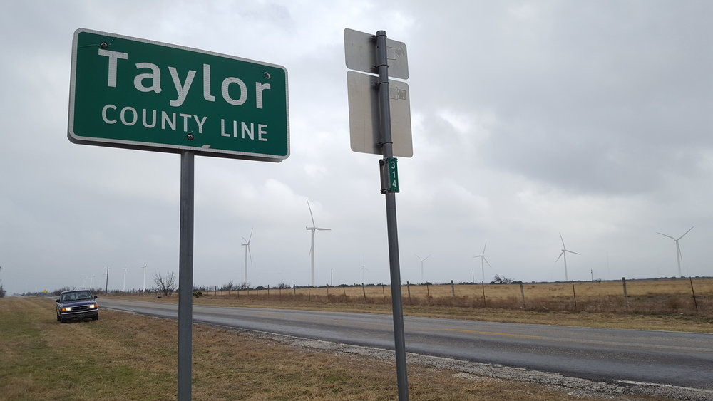 Missed the sign on the way in to Taylor, this is on the Nolan county line, hence the wind farm.
