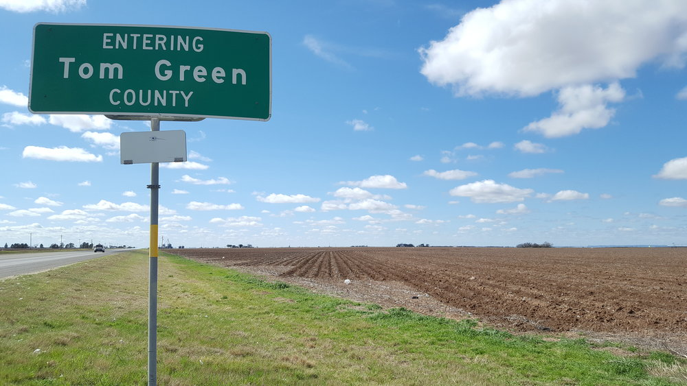 The county sign next to a harvested cotton field.