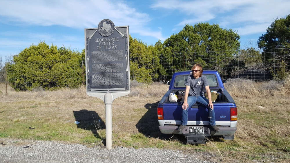 Me sitting on Barney, staring suspiciously at the Geographic Center of Texas marker in McCulloch wearing my Berdoll Pecan farm squirrel shirt that I picked up in Bastrop County. (Photo Credit: Chelsey Clammer, I think she bought me the shirt, too, if I remember correctly)