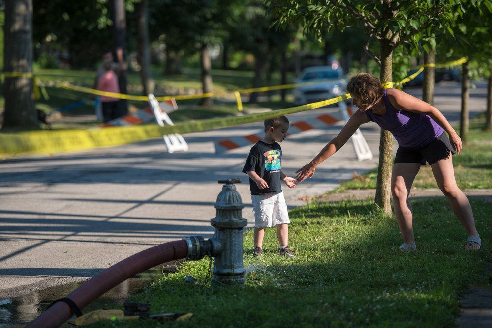 A mother pulls her son away from caution tape surrounding Fernway Elementary School in Shaker Heights, Ohio on July 10, 2018 which caught fire that morning, destroying the roof and attic of the historic building. The building is well loved by the community and people stood around watching the wreckage in disbelief even hours after the fire was extinguished.