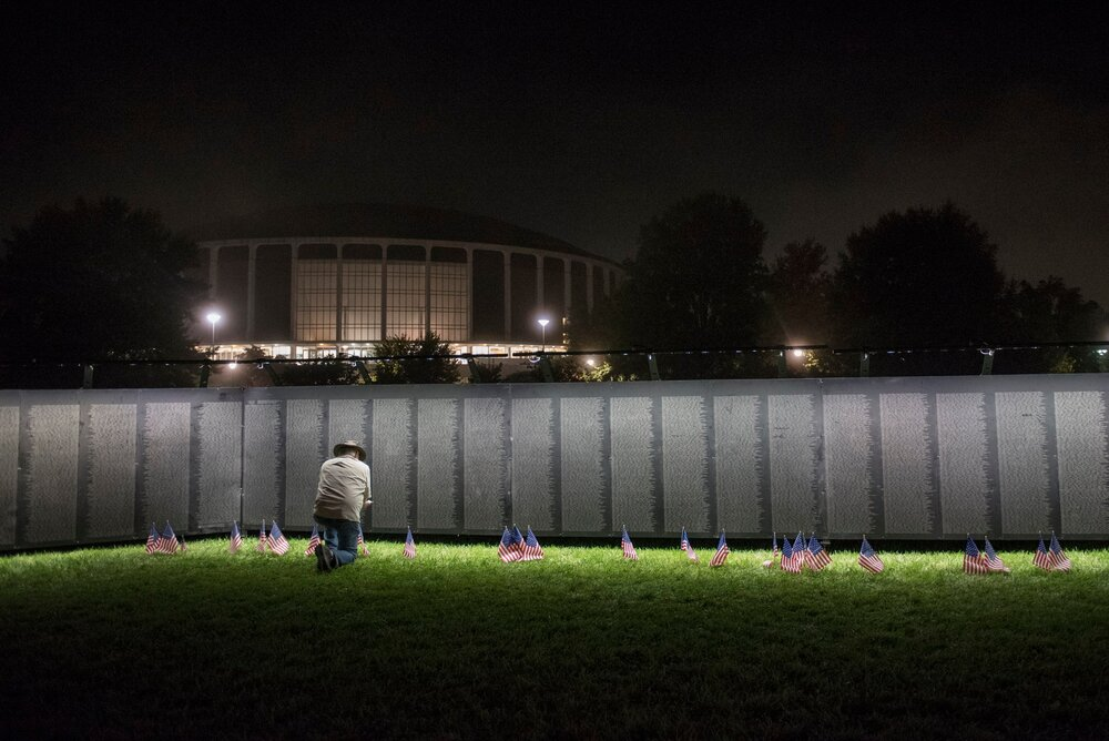 Thad Dye, 69, of Albany, Ohio, kneels by The Wall That Heals, a traveling replica of the Vietnam War Memorial, in Athens, Ohio on Sept. 14, 2017. Dye came to visit the replica to pay respects to friends that died in the war.