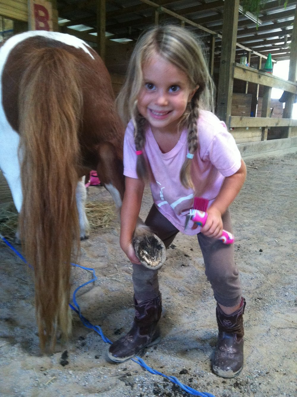 Even the little ones learn how to clean their horse's hooves!