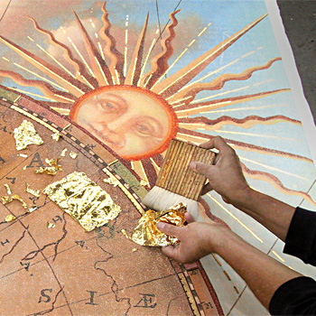 Applying gold leaf to a painted mural surface