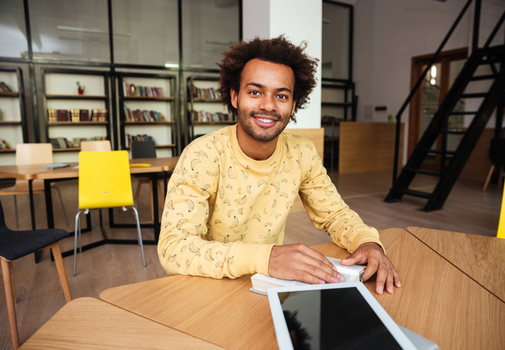 graphicstock-smiling-african-young-man-with-blank-screen-tablet-sitting-at-the-table-and-reading-in-lubrary_SdlS-3B83x.jpg