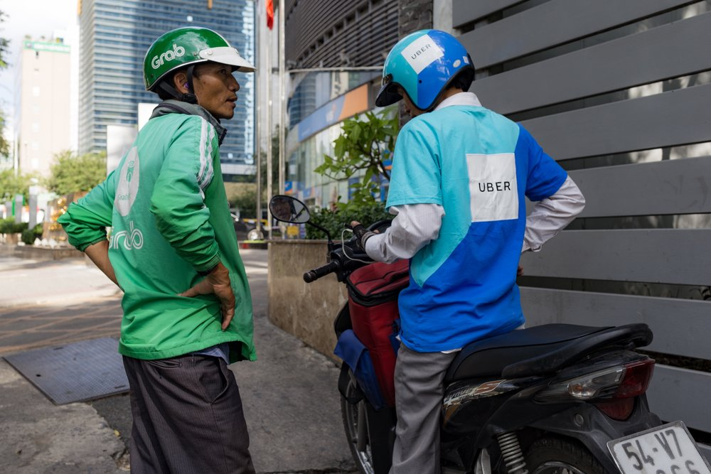 Ride-sharing in Ho Chi Minh, December 2017   Two riders waiting for the next assignment. After Uber's sale of its Southeast Asian stake, Grab is now the largest player in the ride-sharing industry, followed by the Indonesian Go-Jek.