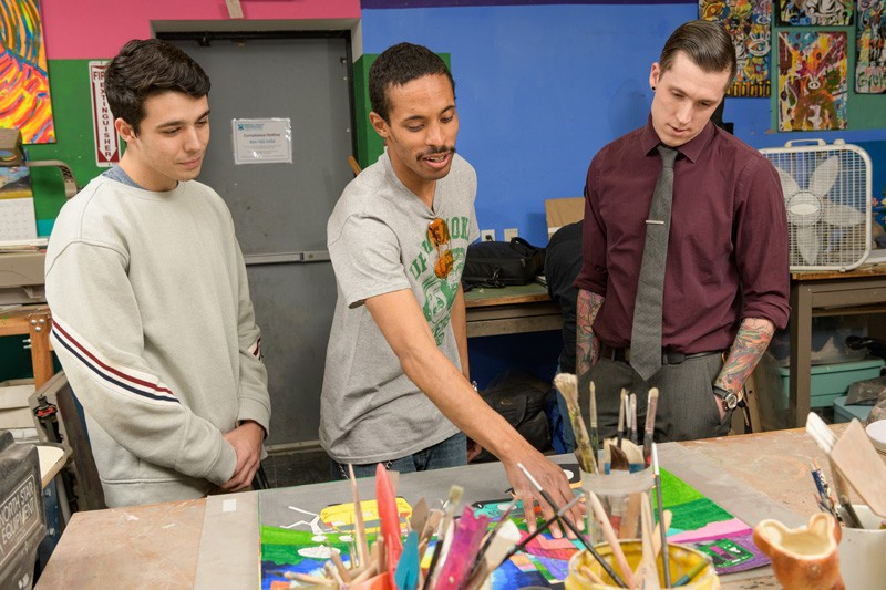 In the Creative Vision Factory's open work space (from left), UD undergraduate Dillon DiGuglielmo, artist Geraldo Gonzalez and graduate student Joshua Stout look over some of Gonzalez's work. Gonzalez, whose artwork has a transportation theme, was also enrolled as a student in the class.