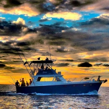 The fishing crew and happy guests of Ruthless, Ruthless Roatan Charters flagship vessel, enjoy the sunset over the Caribbean after a day of deep sea fishing!