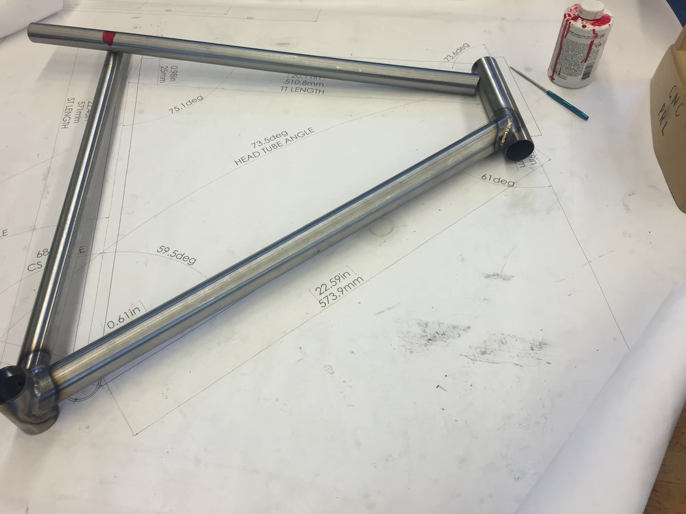 Following the welding of the down tube and seat tube to the bottom bracket, the frame dimensions are then compared to the engineering drawing.