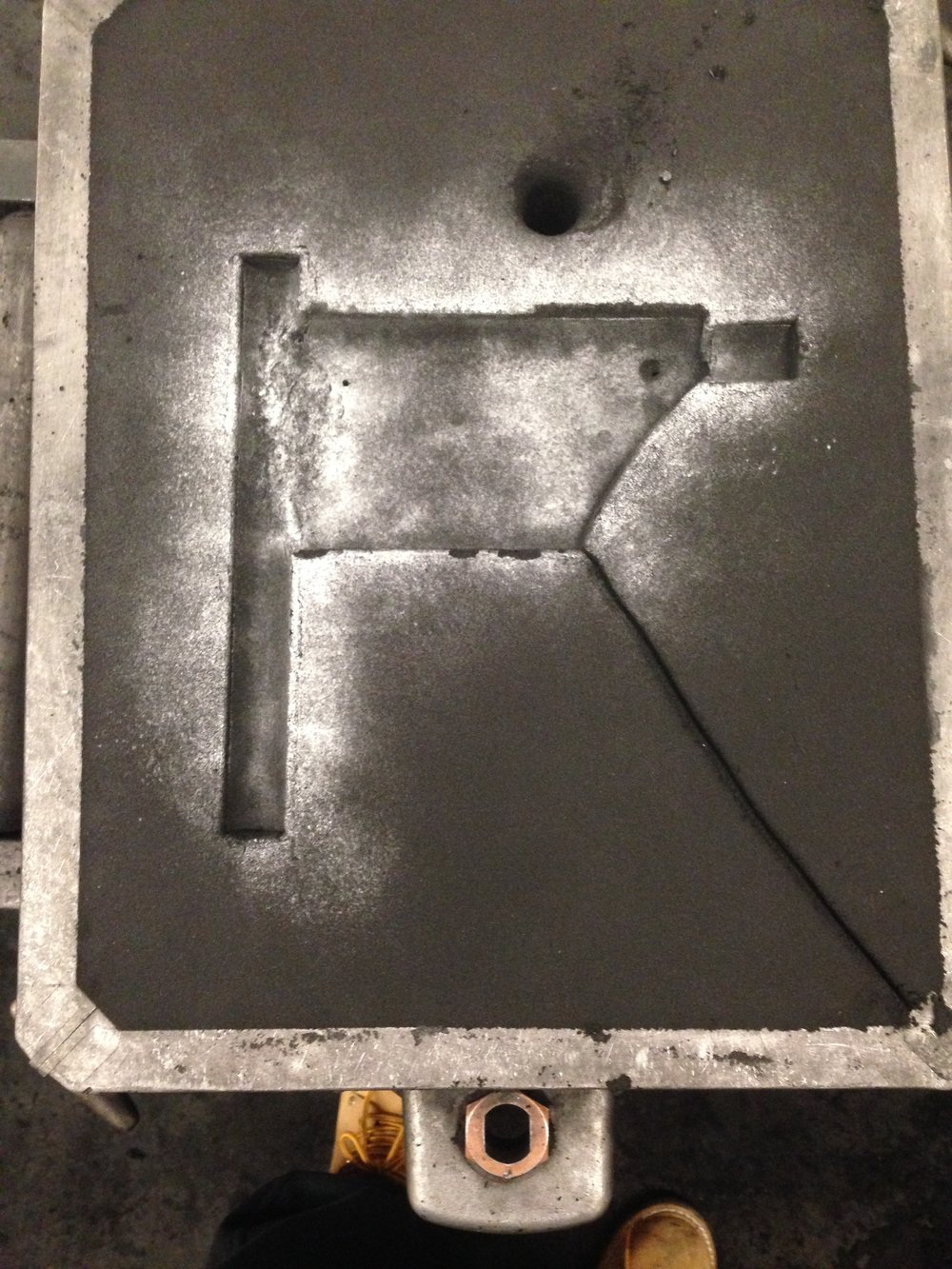 Cope for sand casting with sprue hole and venting channels.
