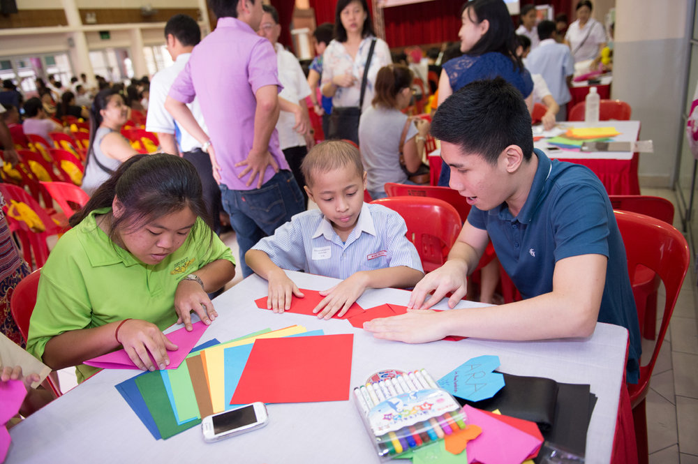 (Above) Joyce (left) and Roy (right) patiently teaching an award winner to fold a heart origami at one of the fringe booths.