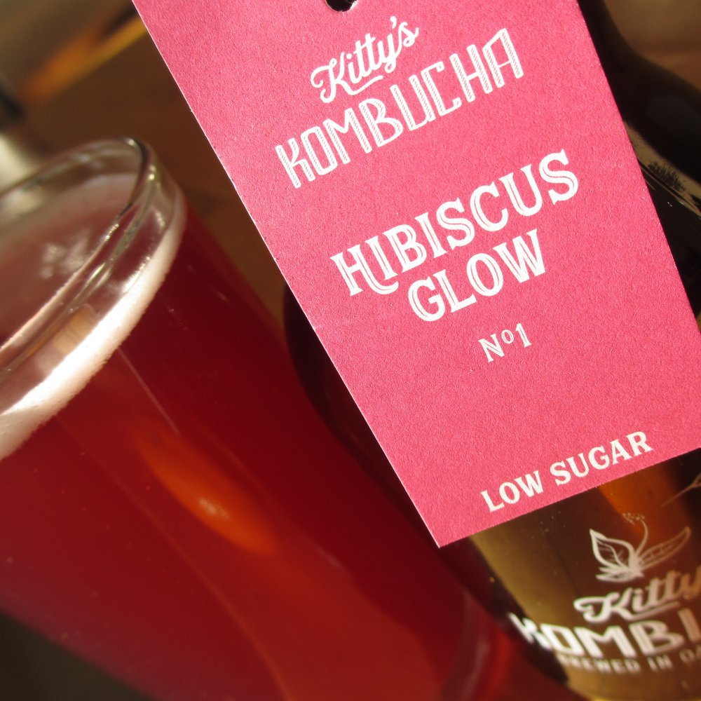 HIBISCUS GLOW  NO.1  Low in sugar... high in energy.  All-year mulled wine celebration in a kombucha, thanks to the punch of hibiscus and familiar spices of the festive season. An original Kitty's Kombucha recipe from Thailand.  Hand crafted with sencha green tea, spices and cane sugar (all organic),  Hibiscus Glow  is a traditionally brewed kombucha in oak barrels, infused for 2nd fermentation with a tisane (herbal tea) of red hibiscus, ginger, cardamom, cloves and cinnamon.  And with less than 2.5g of sugar per 100ml, it's  low sugar  & superbly refreshing!  Enjoy cold, perfectly as it is...  Alternatively, create a festive mixer poured on vodka & ice.