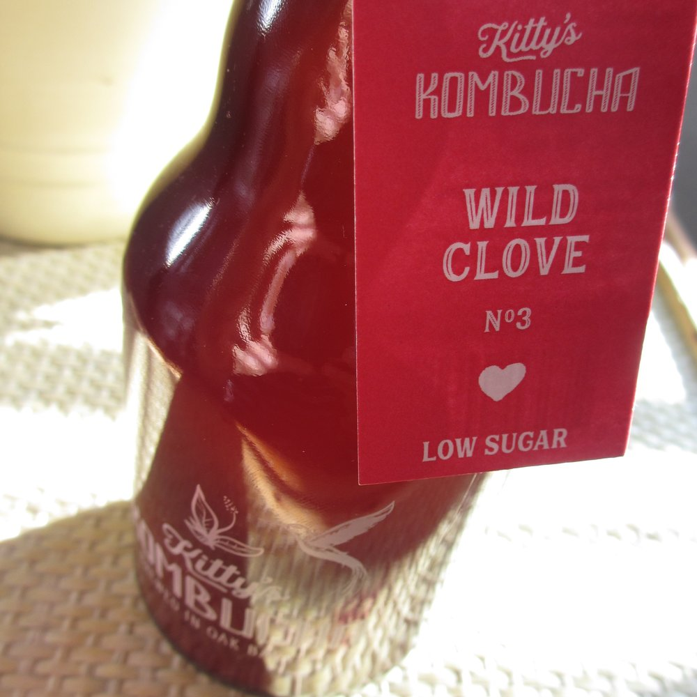 WILD CLOVE  NO.3  *Special Edition*   Sometimes life throws a wild card...  And in this case the Universe gave wild cloves! One day a brew of Hibiscus Glow evolved with a delightful life of its own.  For aficionados of clove only (even if you don't know it).  Hand crafted with sencha green tea, spices and cane sugar (all organic),  Wild Clove  is a traditionally brewed kombucha in oak barrels, infused for 2nd fermentation with a tisane (herbal tea) of red hibiscus, ginger, cloves, cardamom, and cinnamon.  And with less than 2.5g of sugar per 100ml, it's  low sugar  & has all the pzazz!  Enjoy cold, perfectly as it is...  Alternatively, create a bright mixer on gin & ice, or whichever way you wish.