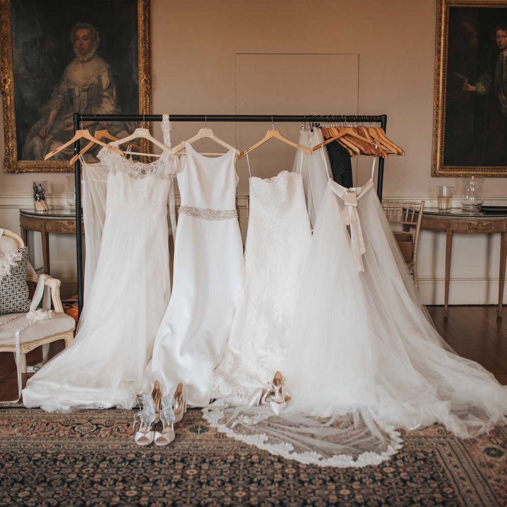 Beautiful Satin Wedding dresses laid out ready to put on draped over the back of a chair