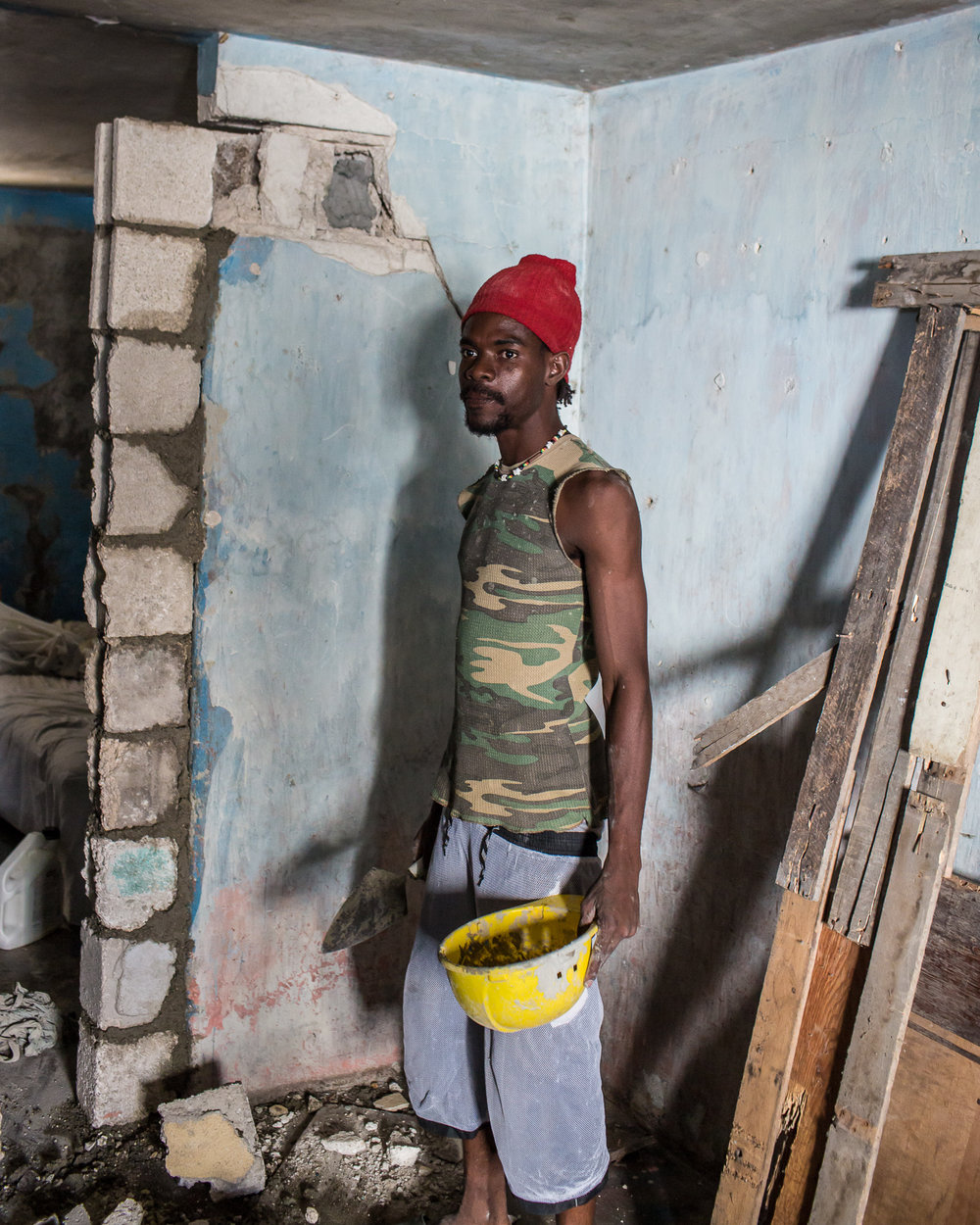 Steevenson Deus poses for a portrait while repairing his earthquake-damaged home on Thursday, December 18, 2014 in Port-au-Prince, Haiti. Fort National was among the hardest hit areas of Port-au-Prince in the 2010 earthquake, but rebuilding has been slow to non-existent. Residents still mostly lack electricity and running water.