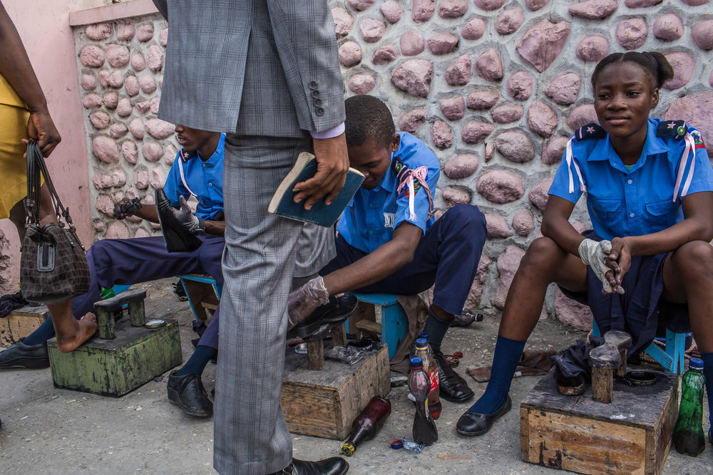 Children shine shoes to raise money for their church on Sunday, December 14, 2014 in Port-au-Prince, Haiti.