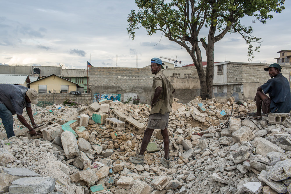 Men salvage usable concrete blocks from the rubble of demolished buildings on Sunday, December 14, 2014 in Port-au-Prince, Haiti. Several square blocks of residences and small businesses have been demolished near the city center, with no warning to residents or compensation for renters, to make way for an expected development project.