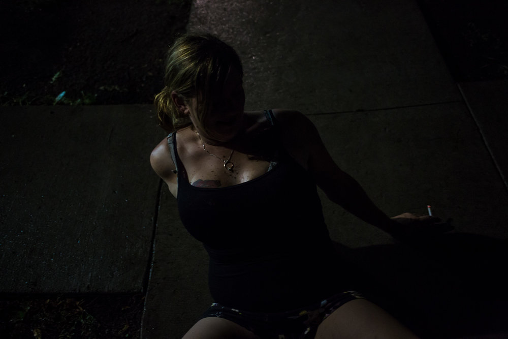 Amanda Wasko smokes a cigarette while sitting on the sidewalk on Thursday, July 25, 2013 in Webster City, IA.