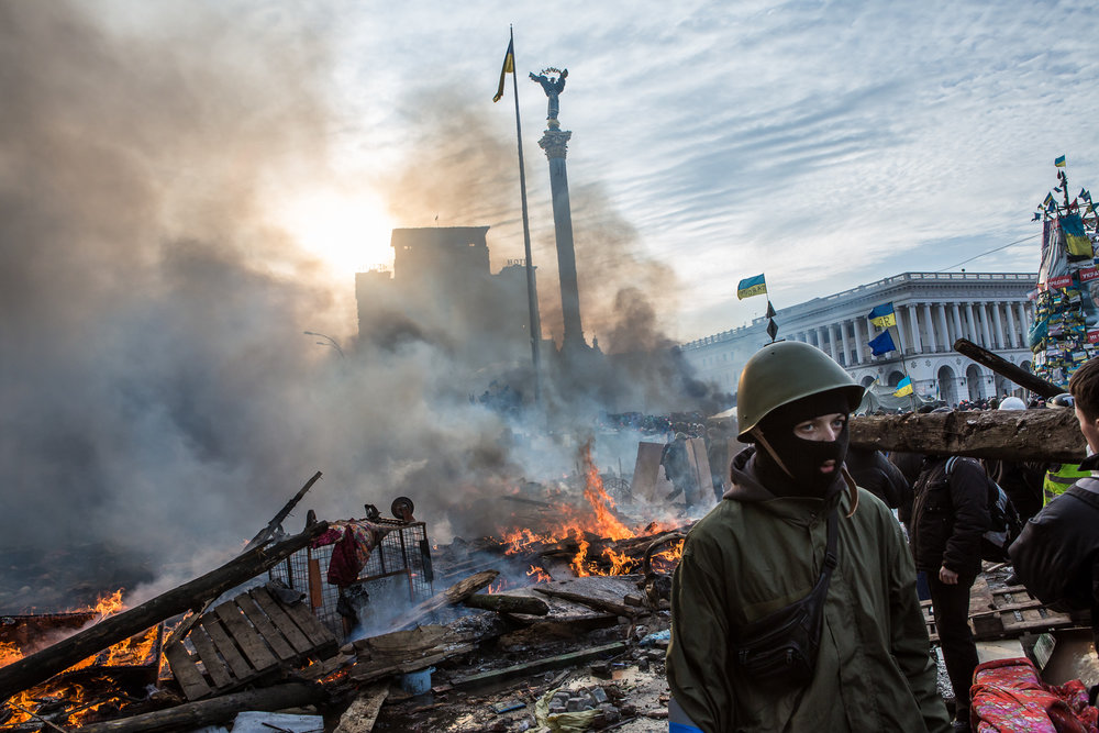 Anti-government protesters walk amid debris and flames near the perimeter of Independence Square, known as Maidan, on February 19, 2014 in Kiev, Ukraine. After several weeks of calm, violence has again flared between police and anti-government protesters, who are calling for the ouster of President Viktor Yanukovych over corruption and an abandoned trade agreement with the European Union.