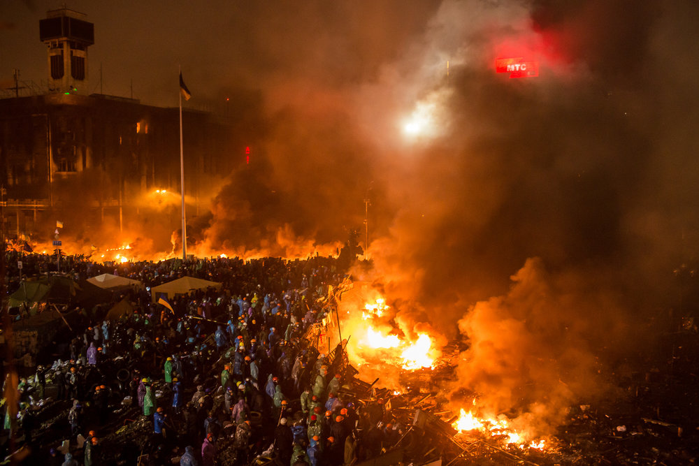 Anti-government protesters stand behind a line of burning tires and debris on Independence Square on February 19, 2014 in Kiev, Ukraine. After several weeks of calm, violence has again flared between anti-government protesters and police as the Ukrainian parliament is meant to take up the question of whether to revert to the country's 2004 constitution.