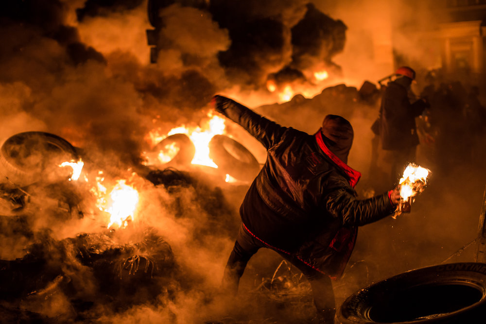 An anti-government protester throws a Molotov cocktail during clashes with police on Hrushevskoho Street near Dynamo stadium on January 25, 2014 in Kiev, Ukraine. After two months of primarily peaceful anti-government protests in the city center, new laws meant to end the protest movement have sparked violent clashes in recent days.