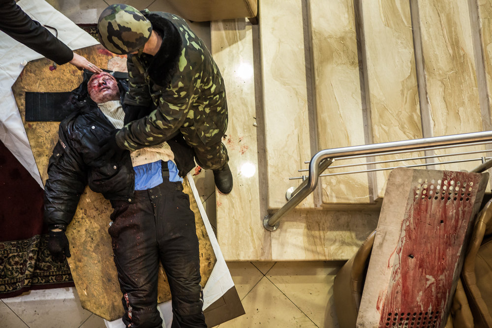 A priest blesses a gravely wounded anti-government protester after medics stopped trying to save him in the lobby of the Hotel Ukraine, which has been converted to a medical clinic and makeshift morgue, on February 20, 2014 in Kiev, Ukraine. After several weeks of calm, violence has again flared between anti-government protesters and police, with dozens killed.