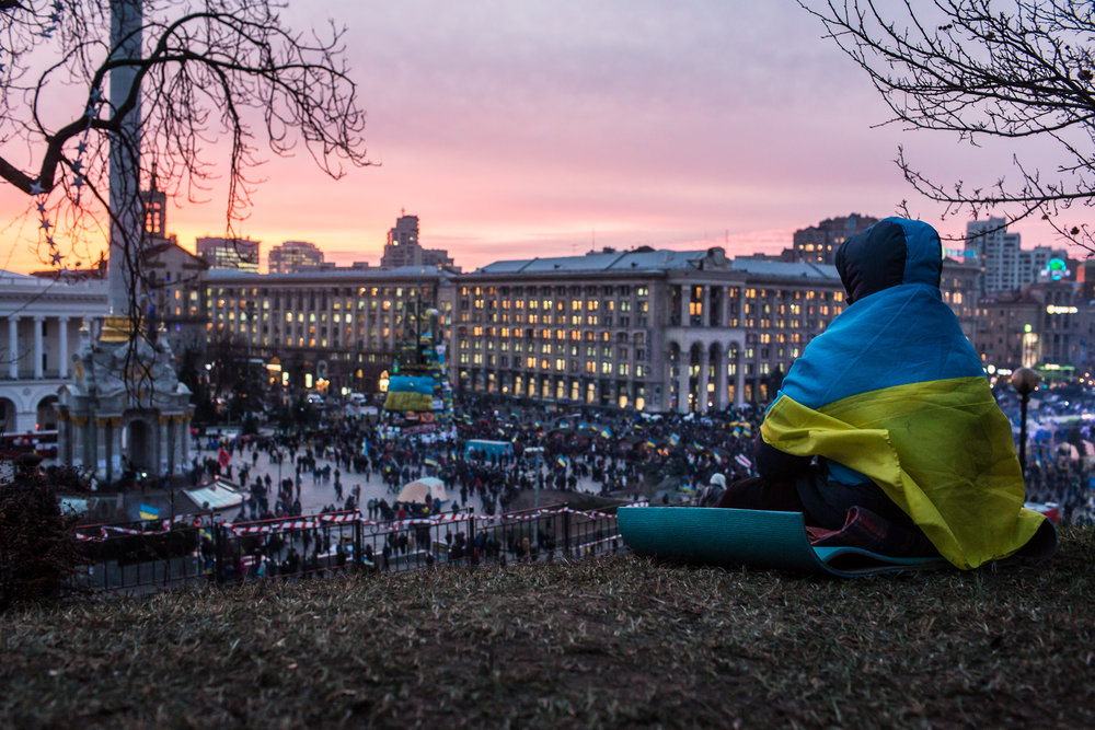 A person wrapped in a Ukrainian flag watches the sun set over Independence Square on December 4, 2013 in Kiev, Ukraine. Thousands of people have been protesting against the government since a decision by Ukrainian president Viktor Yanukovych to suspend a trade and partnership agreement with the European Union in favor of incentives from Russia.