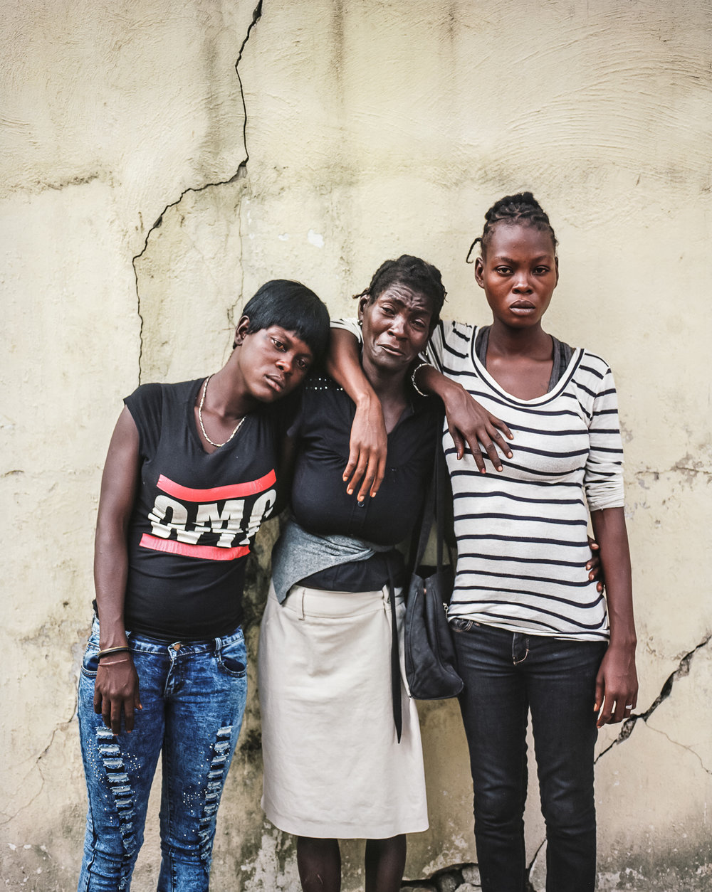 Betty Nicolas, 23, Claudiani Fonrose, and Bertha Nicolas, 20, from left, pose for a picture on Monday, December 15, 2014 in Port-au-Prince, Haiti. They are the sisters and mother of Jolin Nicolas, 19, who was killed while participating in an anti-government protest on December 13.