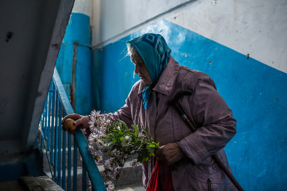 Nadezhda Panasyk, 75, in the stairwell of her apartment building near Donetsk airport. Donetsk, Ukraine. October 2014.