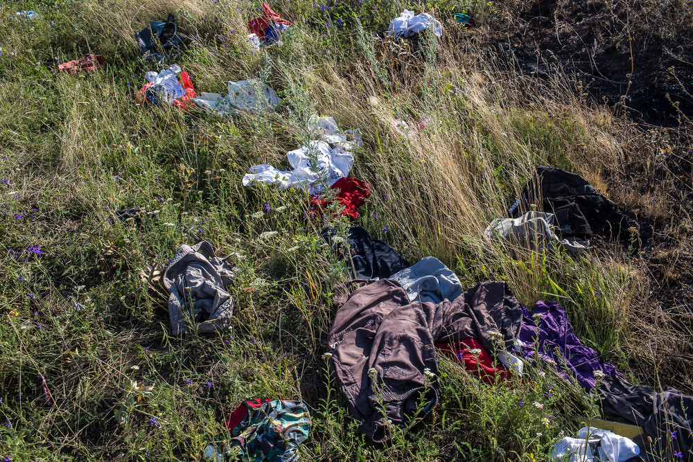 The clothing of passengers on Malaysia Airlines flight MH17 scattered on the ground following the plane's crash. Grabovo, Ukraine. July 2014.
