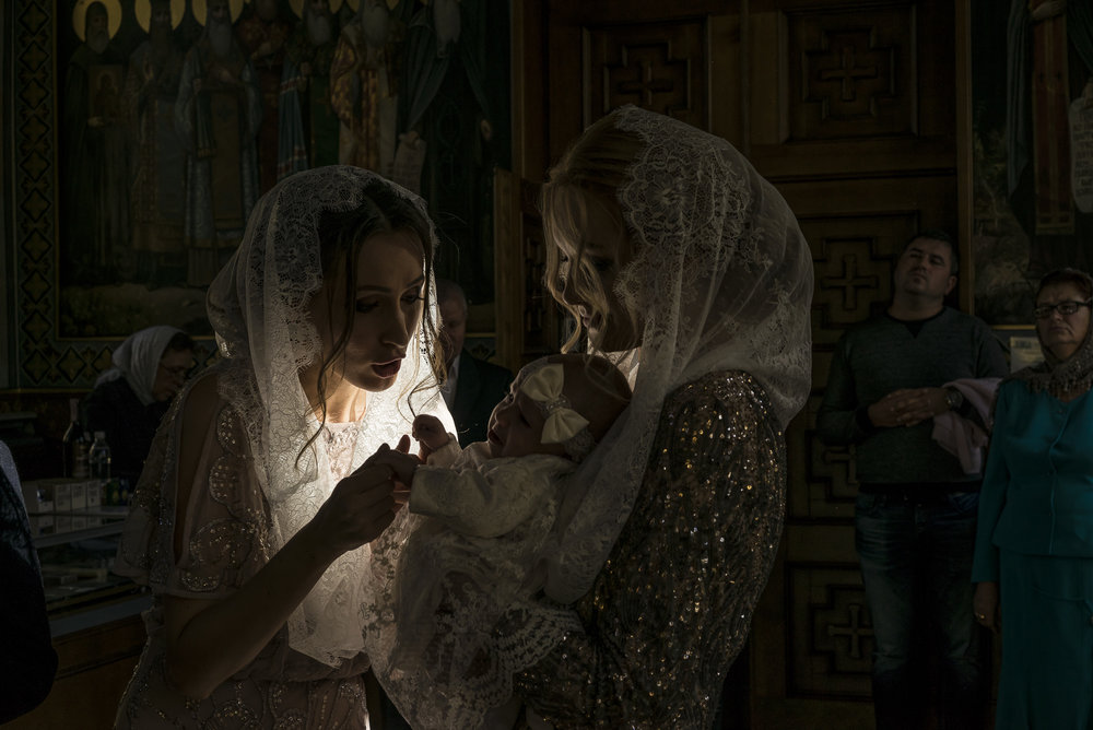 Godmother Ala Oriekhovych tries to comfort Alisa, age three months, in her mother Taisia Melnyk's arms, during her baptism at the Life Spring Church at the Kyiv-Pechersk Lavra on Saturday, October 6, 2018 in Kyiv, Ukraine.