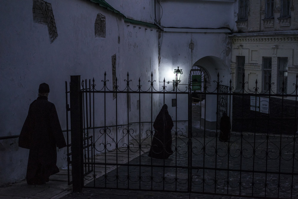 A monk and a nun walk through the darkened streets after leaving a mass at the Kyiv-Pechersk Lavra on Saturday, October 6, 2018 in Kyiv, Ukraine.
