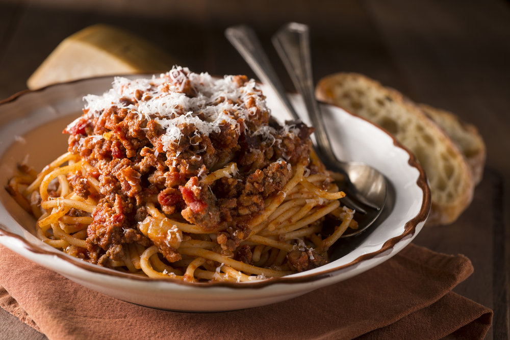 Italian Bolognese pasta with grated parmesan cheese.