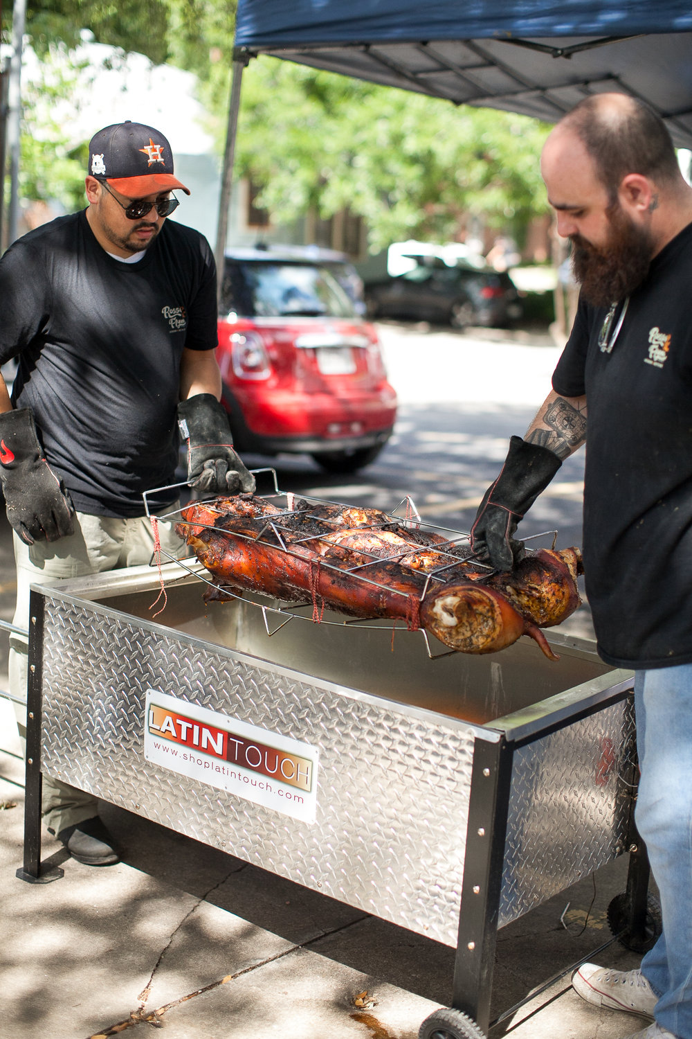 Flipping a whole pig in a caja china