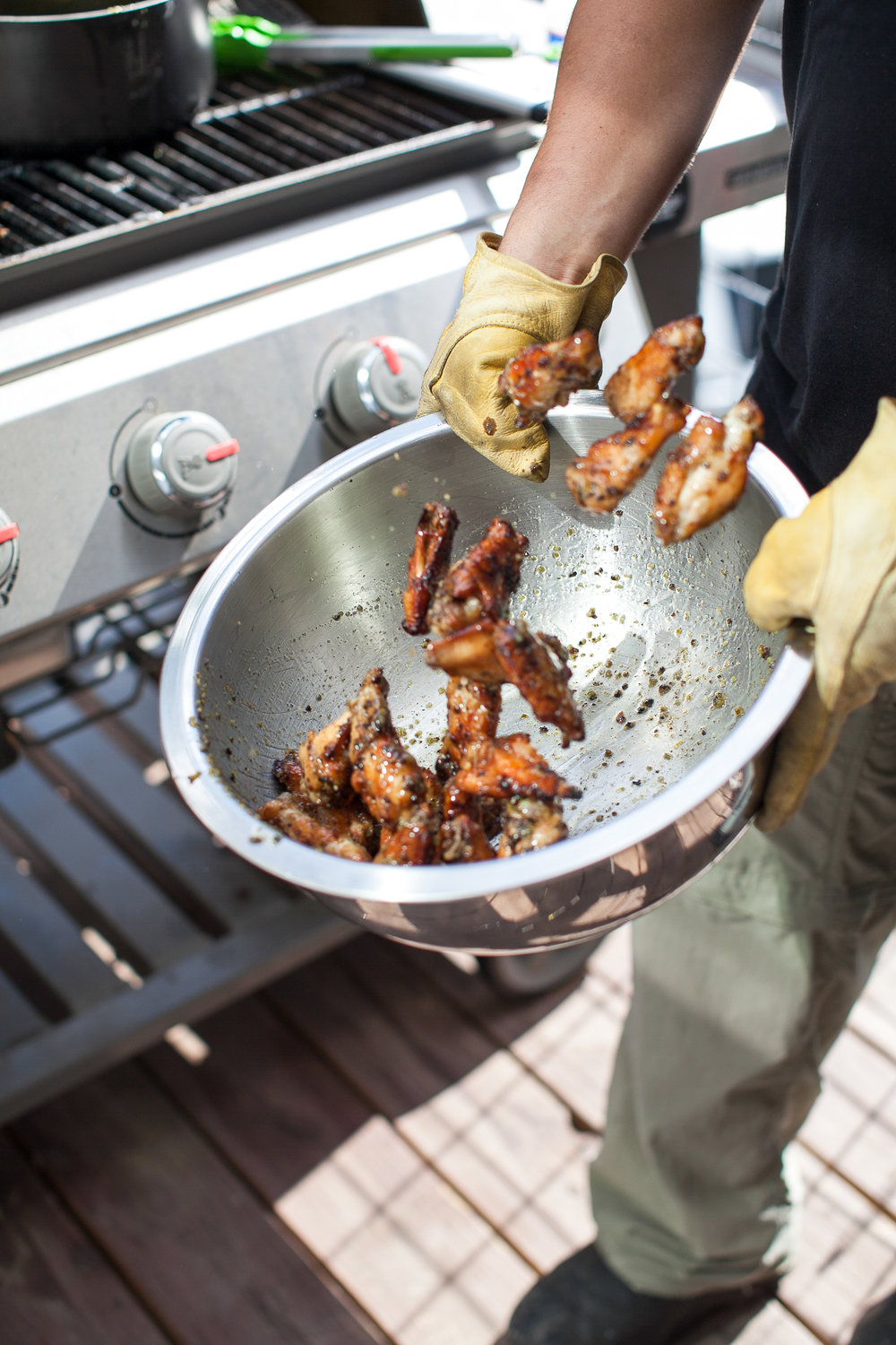 Chicken wings being tossed in butter and sambal sauce in a bowl