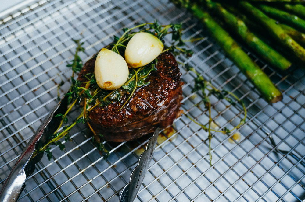 Filet mignon  presented with herbs and garlic.