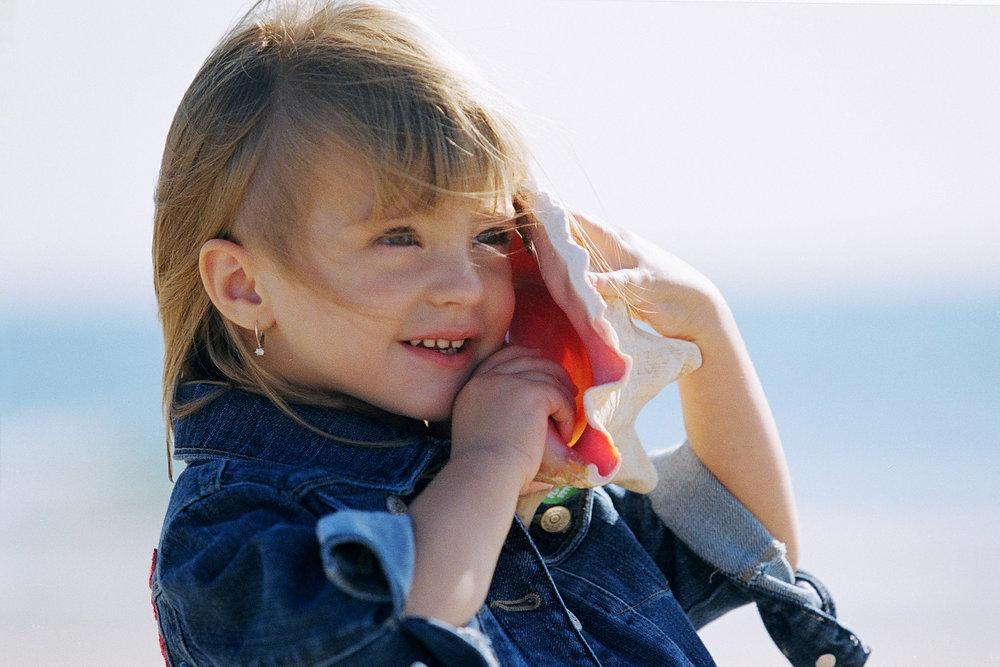 child_beach_listening_to_seashell.jpg