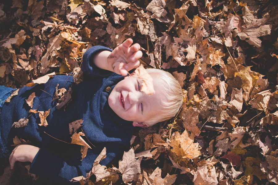 boys playing in fall leaves
