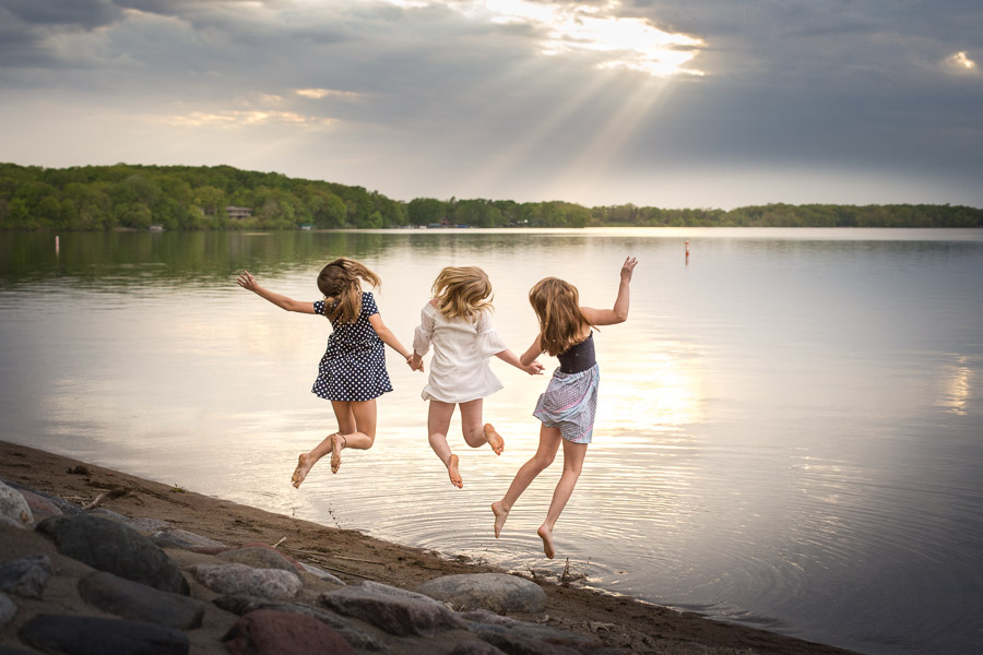 tween girls jumping in a lake - twin cities family photographer