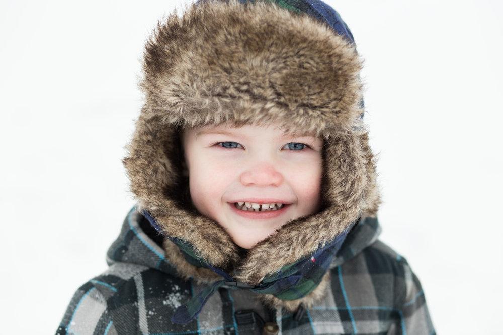 little boy wearing winter hat in snow - wayzata family photographer