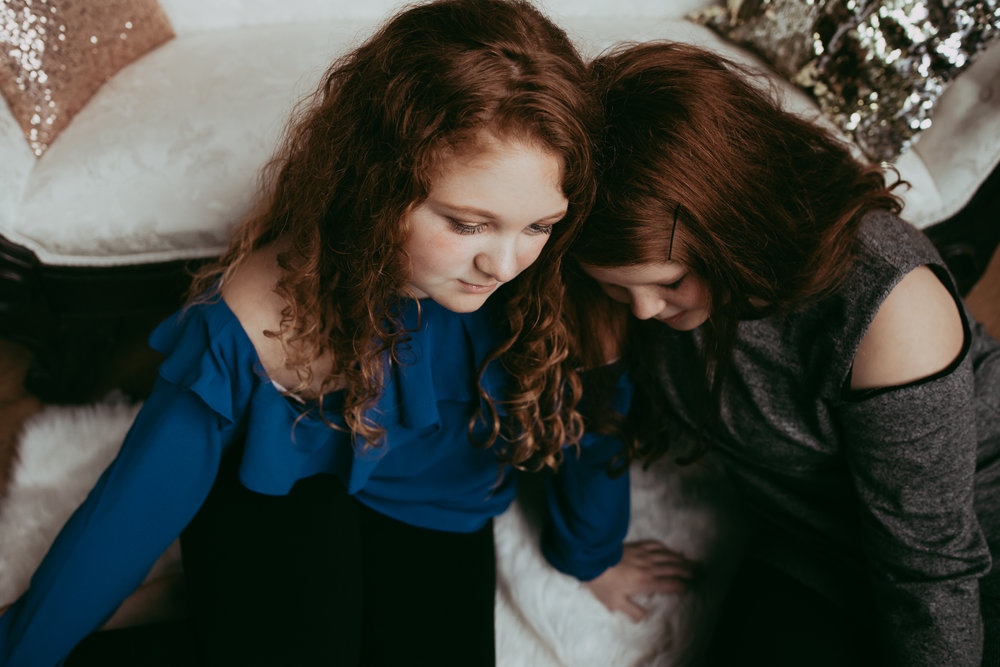 red haired sisters cuddling by white couch - Minneapolis Family Photography
