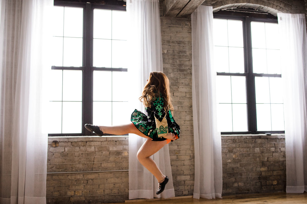 Irish dancer in green dress jumping - Family Lifestyle Photography Minnetonka