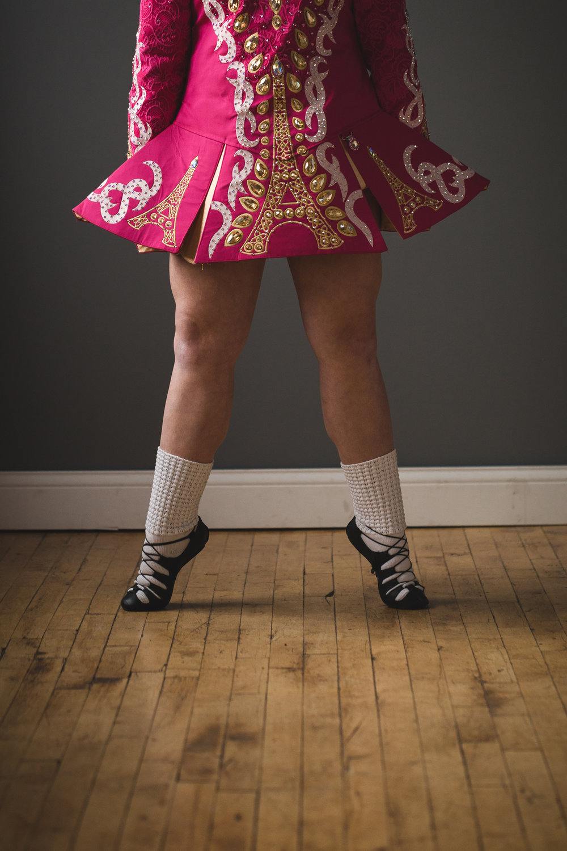 legs of Irish dancer in dark pink dress -
